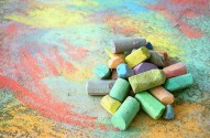 a collection of colorful sidewalk chalk is piled up on a rainbow drawing outside on the pavement.