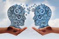 Business technology concept as two hands holding a group of machine gears shaped as a human head as a symbol and metaphor for the transfer of industry information or corporate training.