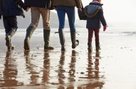 Close Up Of Family Walking Along Winter Beach