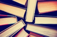 image of a stack of hard back books on the end of the pages toned with a retro vintage warm instagram like filter app or action effect