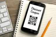 discount coupon qr code on mobile phone, with desk background