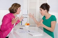 Two business woman disputing in the office having disagreement - problems on workplace.