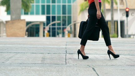 Cropped view of business woman walking in city street with laptop bag commuting and going to work in the morning. Copy space waist down