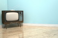 An old vintage television set in the corner of an empty room with light blue wall and a reflective wooden floor