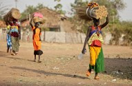 TORIT, SOUTH SUDAN-FEBRUARY 20 2013: Unidentified women carry heavy load on their heads in Torit, South Sudan.
