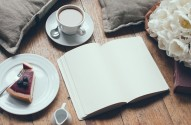 Pillows, a bouquet of tulips, coffee with milk, cheesecake, paper note pad on a shabby wooden floor. Hipster lifestyle