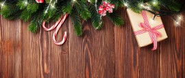 Fir tree branch with christmas lights, gift box and candy canes on wooden background with copy space