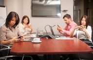 Group of people sitting in a meeting room and being distracted by their smartphones ** Note: Shallow depth of field