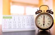 Alarm clock  and calendar on bright background